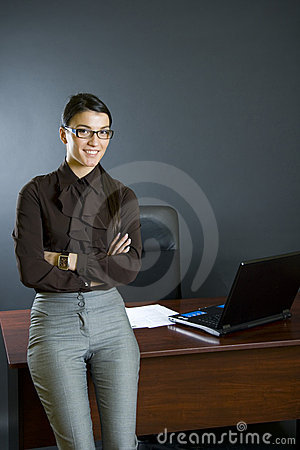 Attractive businesswoman against office desk