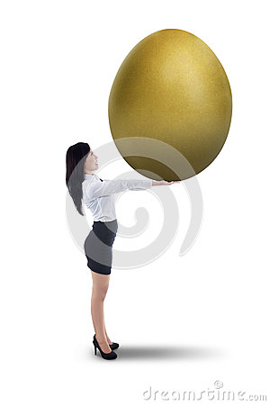 Attractive businesswoman holding big golden egg -