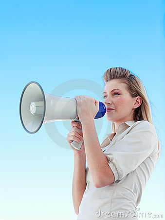 Attractive businesswoman shouting in a megaphone