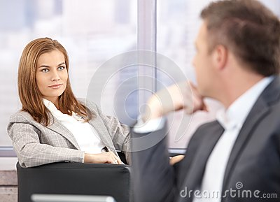 Attractive businesswoman smiling at businessman