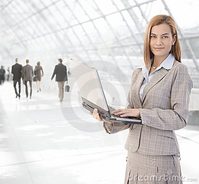 Attractive businesswoman using laptop at passage