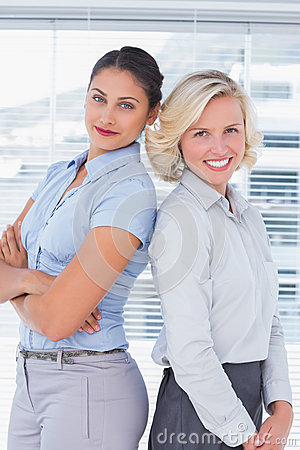 Attractive businesswomen with arms crossed standing back to back