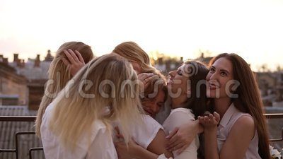 Attractive caucasian girls are hugging standing outside on a terrace or balcony. Six beautiful young women in white. Shirts and with red lipstick. Hen party stock video footage