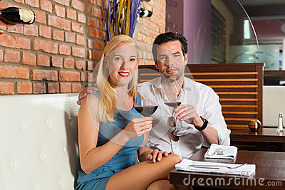 Attractive couple drinking red wine in bar
