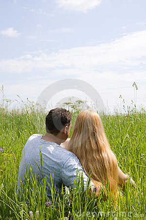Attractive couple enjoying togetherness on meadow