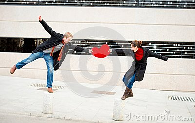 Attractive couple fighting over a love heart pillow
