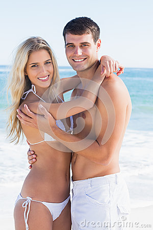 Attractive couple hugging and smiling at camera