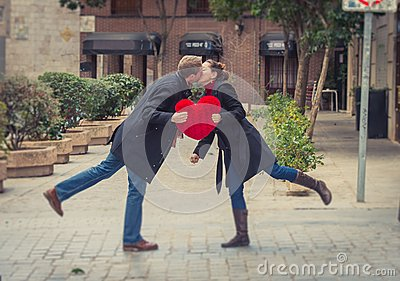 Attractive couple kissing with a red heart pillow