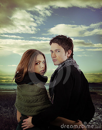 Attractive couple in nature against dramatic sky