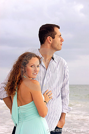 Attractive couple at ocean he is looking at sea sh