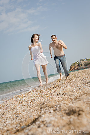 Attractive couple is running along the beach