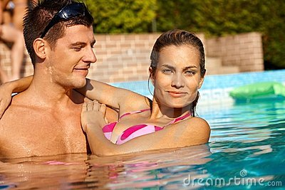 Attractive couple in swimming pool smiling