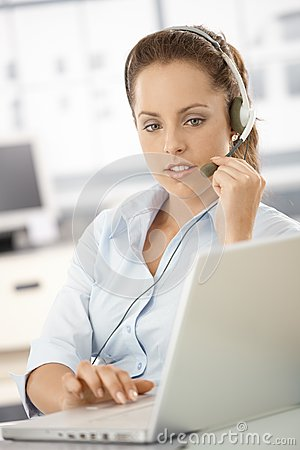 Attractive customer servicer using headphones