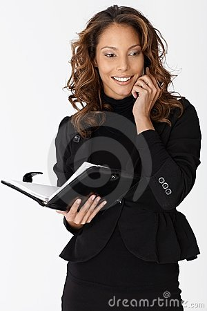 Attractive ethnic businesswoman on mobile smiling