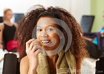 Attractive ethnic girl eating apple at gym