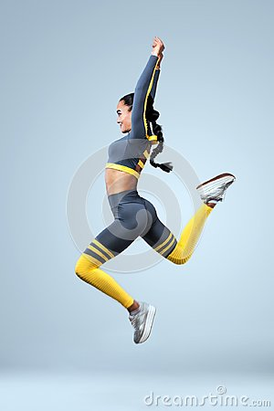 Free Attractive Excited Fitness Girl Dancer In Sportwear Jumping Of Joy Isolated Over Gray Background Stock Image - 103234861