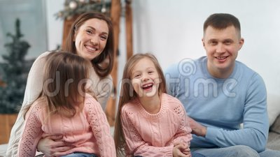 Attractive family posing with Christmas decoration at home laughing looking at camera. Medium closeup. Happy mother father and two little daughter smiling stock video footage