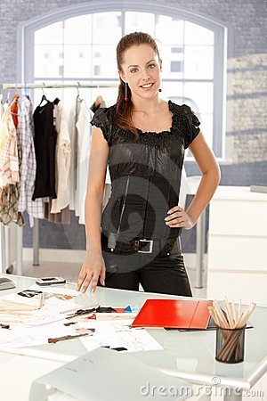 Attractive fashion designer standing by desk