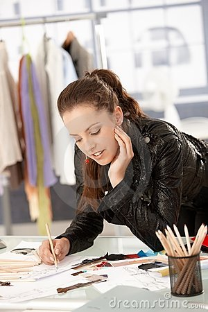 Attractive fashion designer working in studio