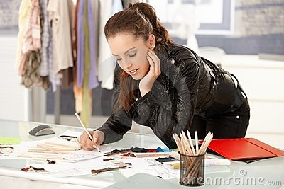 Attractive fashion designer working in studio