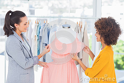 Attractive fashion designers adjusting a dress