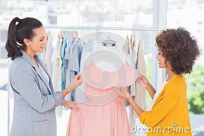 Attractive fashion designers adjusting a dress