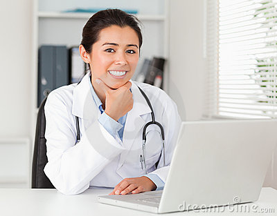 Attractive female doctor working with her laptop