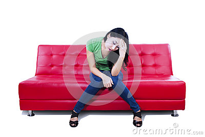 Attractive female feel depressed on red sofa - isolated