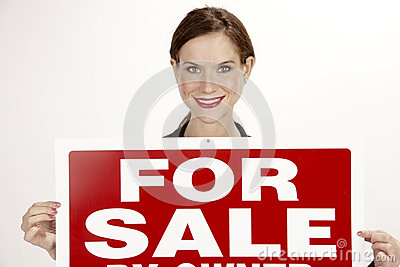 Attractive Female Realtor Holds up the For Sale Sign