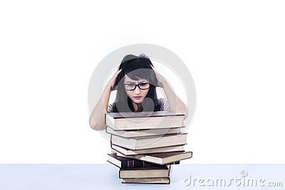 Attractive female student stress looking at books - isolated