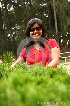 Attractive female wearing shades behind bushes
