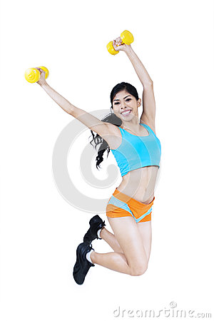 Attractive fitness woman jumping with dumbbell