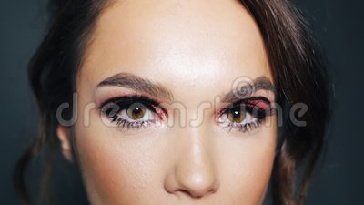 attractive girl with bright makeup on eyes winking young