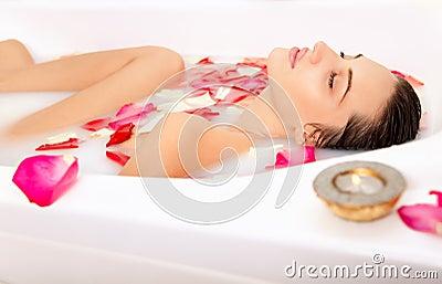 Attractive girl enjoys a bath with milk