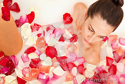 Attractive girl enjoys a bath with milk and roses