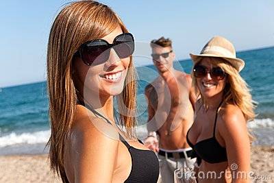 Attractive girl with friends on beach.
