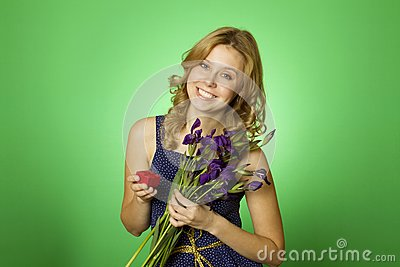 Attractive girl holding flowers and a gift box