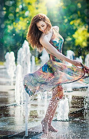 Free Attractive Girl In Multicolored Short Dress Playing With Water In A Summer Hottest Day. Girl With Wet Dress Enjoying Fountains Stock Images - 43395034