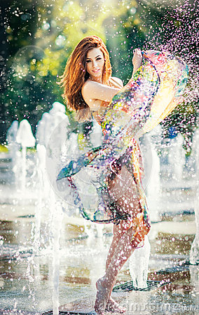 Free Attractive Girl In Multicolored Short Dress Playing With Water In A Summer Hottest Day. Girl With Wet Dress Enjoying Fountains Stock Photos - 43395053