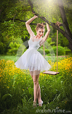 Free Attractive Girl In White Short Dress Posing Near A Tree Swing With A Flowery Meadow In Background. Blonde Young Woman Royalty Free Stock Photography - 43572887
