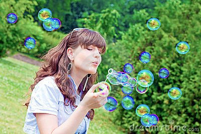 Attractive girl inflating colorful soap bubbles