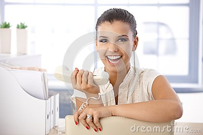 Attractive girl laughing with receiver in hand