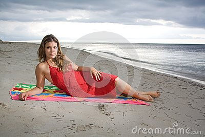 Attractive girl laying on a towel with red dress