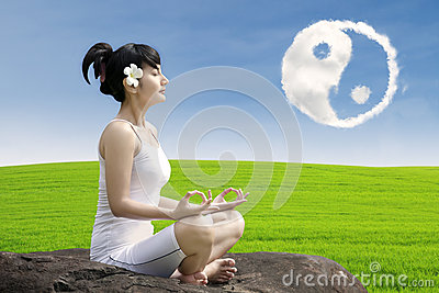 Attractive girl meditate yoga under ying yang cloud