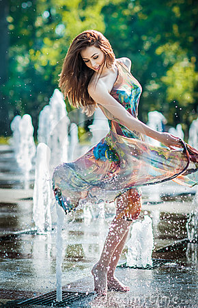 Attractive girl in multicolored short dress playing with water in a summer hottest day. Girl with wet dress enjoying fountains