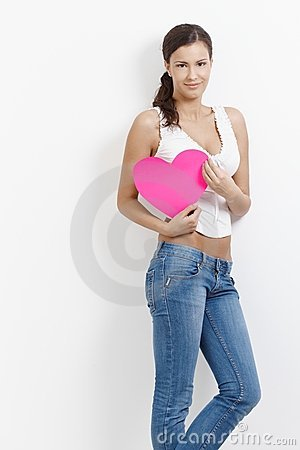 Attractive girl with pink heart in hands smiling
