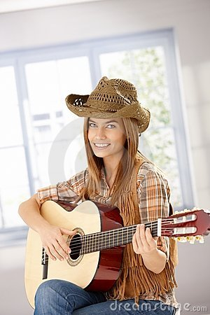 Attractive girl playing guitar smiling