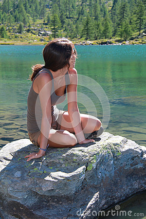 Attractive girl poses on a stone in alpine lake