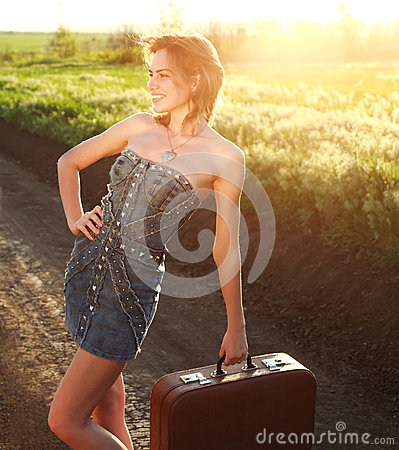 Attractive girl posing with suitcase at countryside