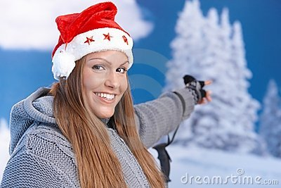 Attractive girl in santa hat pointing to landscape